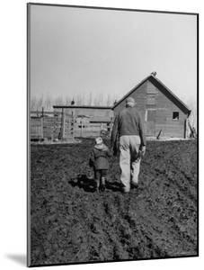 Grandpa and 4 Year Old Granddaughter, on Morning Chores, to Feed Pigs on Nearby Lot by Gordon Parks