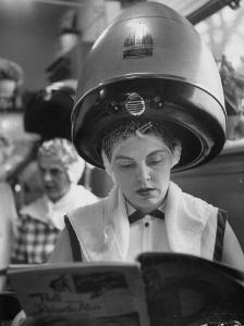 Woman Sitting under Hair Dryer Reading a Magazine by Gordon Parks