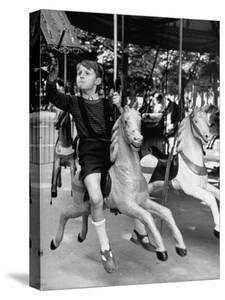 Young Turkish Prodigy Hassan Kaptan Riding a Merry Go Round by Gordon Parks