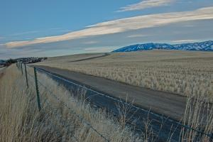 A Road Cuts Through Harvested Wheat Fields as Lenticular Clouds Hover over the Bridger Mountains by Gordon Wiltsie