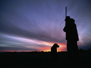 A Silhouetted Hunter and His Dog at Twilight by Gordon Wiltsie