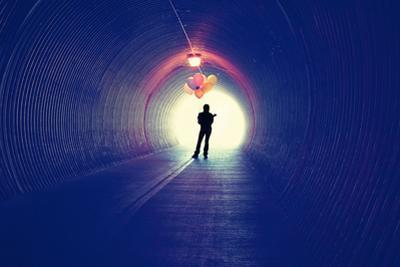 A Girl at the End of a Tunnel Holding Balloons by graphicphoto