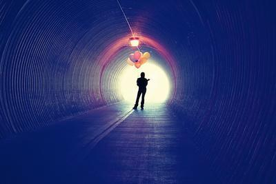 A Girl at the End of a Tunnel Holding Balloons