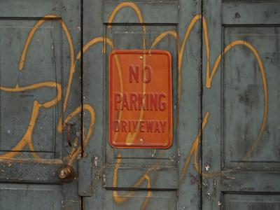 Gray Wooden Doors with Yellow Grafiti Lettering and an Orange Sign--Photographic Print