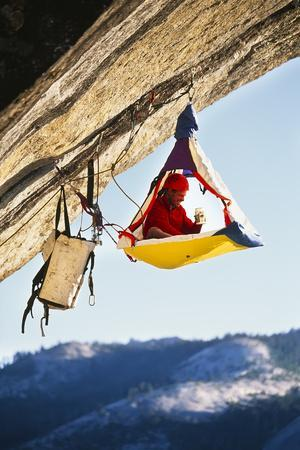 Rock Climber Bivouacked in His Portaledge on an Overhanging Cliff.