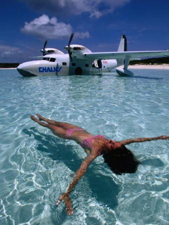 Female Floating in Crystal Waters in Front of Seaplane, Bahamas