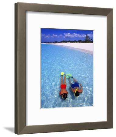 Two People Snorkelling in Blue Water Near Beach