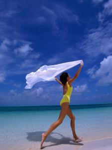 Woman Running on Beach with White Sarong Overhead by Greg Johnston