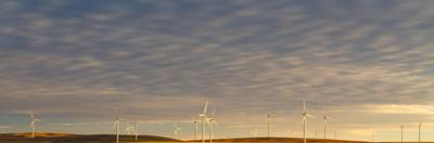 Sunset Light Shining On Wind Turbines Spinning In A Wheat Field by Greg Winston