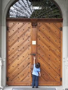 Young Boy Reaches for Door Handle at St. Peter's Church by Greg