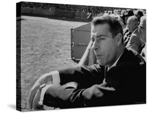 Ex Yankee Baseball Player Joe DiMaggio, Leaning over Rail Watching 3rd Game of the World Series by Grey Villet