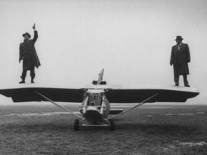 Goodyear Aircraft Engineers Standing on Wings of Rubber Airplane, Can Fly 60 MPH with 200 yd Runway by Grey Villet