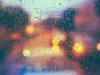 Drops of Rain on Blue Glass Background. Street Bokeh Lights out of Focus. Autumn Abstract Backdrop