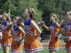 Group of Cheerleaders Cheering in a Field