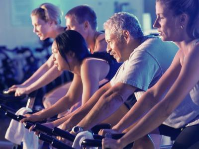 Group of People on Exercise Bikes in a Health Club--Photographic Print