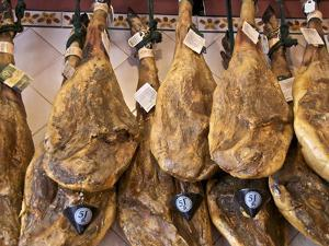 Spanish Hams Hanging in a Restaurant Bodega, Seville, Andalusia, Spain, Europe by Guy Thouvenin