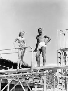 A Man and a Young Woman Stand on a Diving Board in Their Bathing Suits by H^ Armstrong Roberts