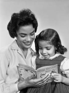 Afro-American Mother and Daughter Looking Down Reading Book Together by H^ Armstrong Roberts