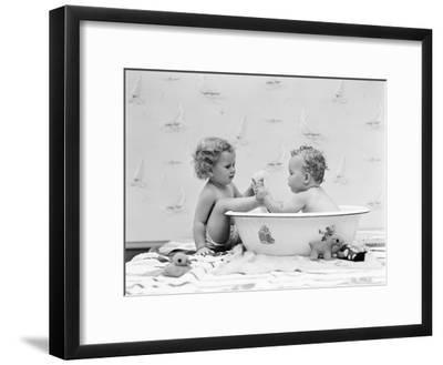 Baby Boy Sittings in Wash Tub, Washing Feet of Girl Sitting Outside of Tub