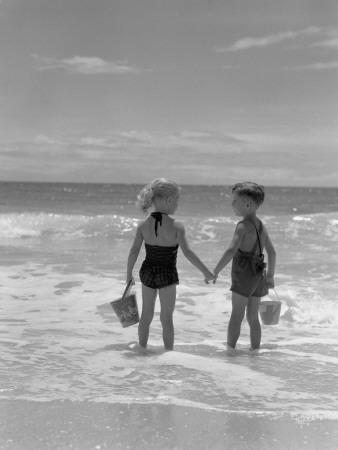 Boy and Girl Standing on Beach, Holding Hands, Rear View