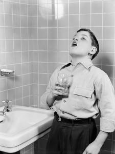Boy Gargling in Bathroom by H. Armstrong Roberts