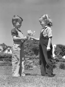 Boy Giving Bouquet of Daisies To Little Girl by H^ Armstrong Roberts