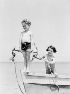 Boy Standing on Bow of Row Boat Holding Anchor, Girl Holding Rope by H. Armstrong Roberts