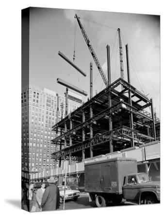 Construction Site For Large Office Building, Cranes Lifting Beams in Background