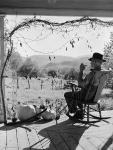 Elderly Farmer Smoking Pipe, Sitting on Rocker on Front Porch Looking Out Onto Land by H^ Armstrong Roberts