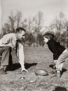 Father and Son Playing Football by H. Armstrong Roberts