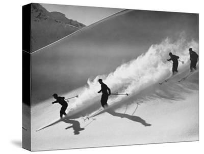 Group of Skiers Descending Alpine Slope, People in Silhouette