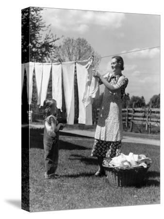 Mother and Daughter Doing Laundry, Hanging Wash on Clothesline in Backyard