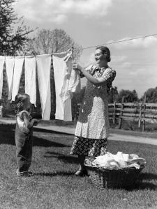 Mother and Daughter Doing Laundry, Hanging Wash on Clothesline in Backyard by H. Armstrong Roberts