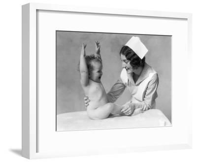 Nurse and Naked Baby With Hands Raised