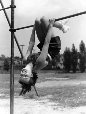 Smiling Teen Girl on Playground Hanging Upside Down on Monkey Bars by H. Armstrong Roberts