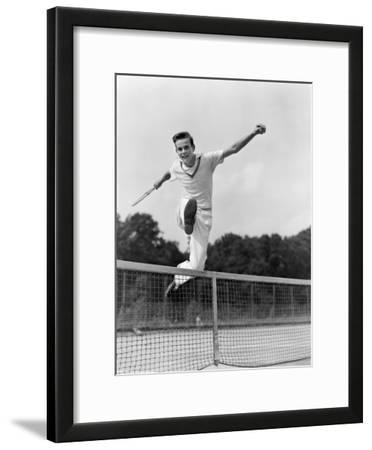 Teen in Tennis Whites Hurdleing the Net With Arms