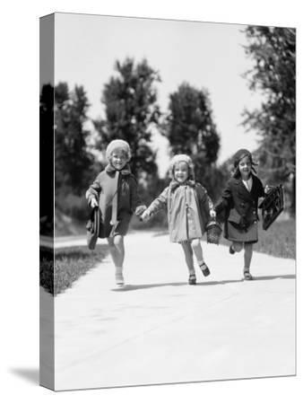 Three Girls Running Along Suburban Sidewalk, Carrying Schoolbags
