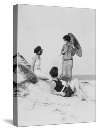 Three Young Women on Beach, Two in Swim Suits, Other Wearing Dress and Carrying a Parasol