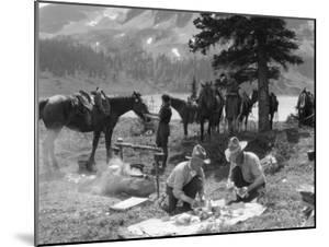 Two Men, Cowboy Guides, Make Campfire and Prepare Food by H. Armstrong Roberts