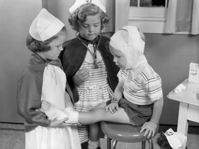 Two Young Girls Dressed As Nurses, Bandaging Three Year Old Boy's Head and Foot