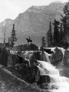 Vertical Waterfall, Man on Horse in Background by H. Armstrong Roberts