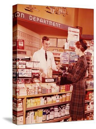 Woman at Pharmacy Counter Talking To Pharmacist