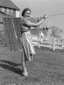 Woman in Apron Smiling As She is Hanging Laundry on Clothesline by H. Armstrong Roberts