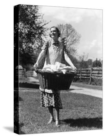 Woman Wearing Apron, Carrying a Wicker Basket of Clean Laundry Outdoors