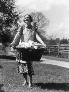 Woman Wearing Apron, Carrying a Wicker Basket of Clean Laundry Outdoors by H. Armstrong Roberts