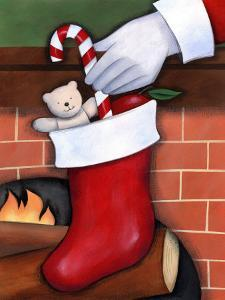 Hand of Santa Claus Placing Candy Cane in Stocking
