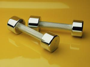 Hand Weights on a Reflective Yellow Surface