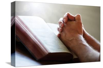 Hands Praying on a Holy Bible--Stretched Canvas Print