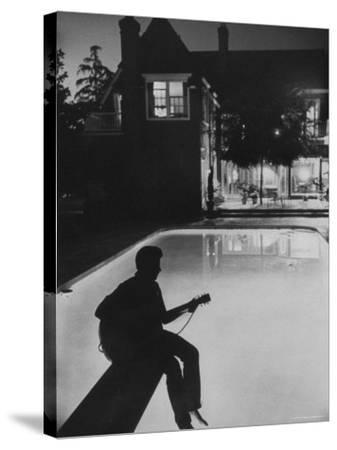 Pop Singer Ricky Nelson Sitting on Diving Board of Family Swimming Pool