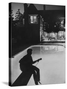 Pop Singer Ricky Nelson Sitting on Diving Board of Family Swimming Pool by Hank Walker